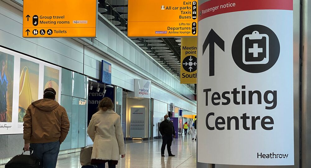 Travellers pass a sign for a COVID-19 test centre at Heathrow Airport, London, Britain, February 13, 2021.