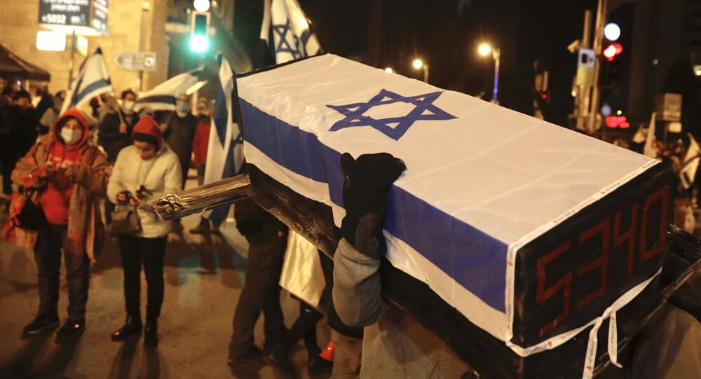 An Israeli protester carries a mock coffin during a demonstration against Israeli Prime Minister Benjamin Netanyahu in Jerusalem, Saturday, Feb. 13, 2021