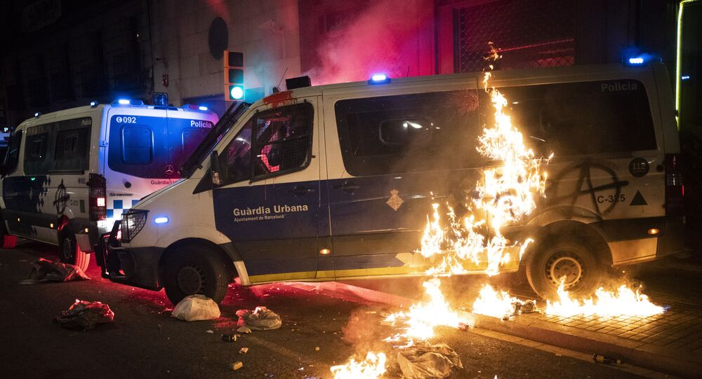 A police van is set on fire as protestors throw molotov cocktails at police during clashes following a protest condemning the arrest of rap singer Pablo Hasél in Barcelona, Spain, Saturday, Feb. 27, 2021.
