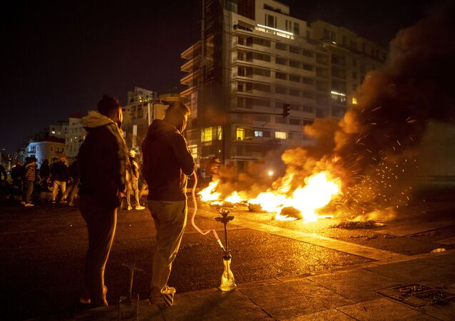 Protesters smoke water pipes in front burning tires that were set on fire to block a road, at Martyrs Square, in downtown Beirut, Lebanon, Saturday, March 6, 2021.