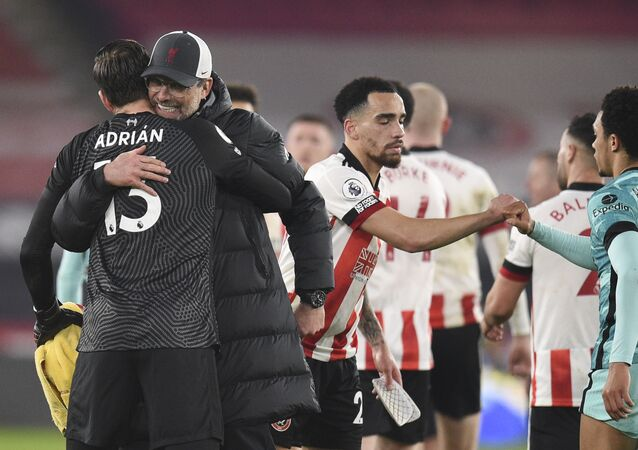 Liverpool's manager Jurgen Klopp hugs Liverpool's goalkeeper Adrian, left, after the English Premier League soccer match between Sheffield United and Liverpool at Bramall Lane stadium in Sheffield, England, Sunday, Feb. 28, 2021.