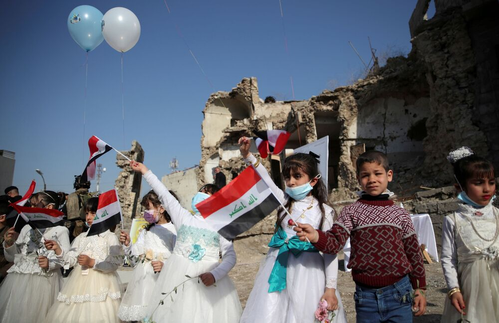 Girls wave national flags as they gather at Church Square ahead of Pope Francis' arrival to visit Mosul, Iraq, 7 March 2021.