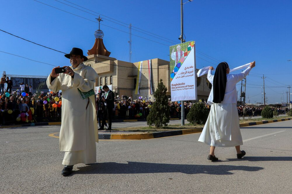 People wait for the arrival of Pope Francis near the Grand Immaculate Church in the town of Qaraqosh, Iraq, 7 March 2021.
