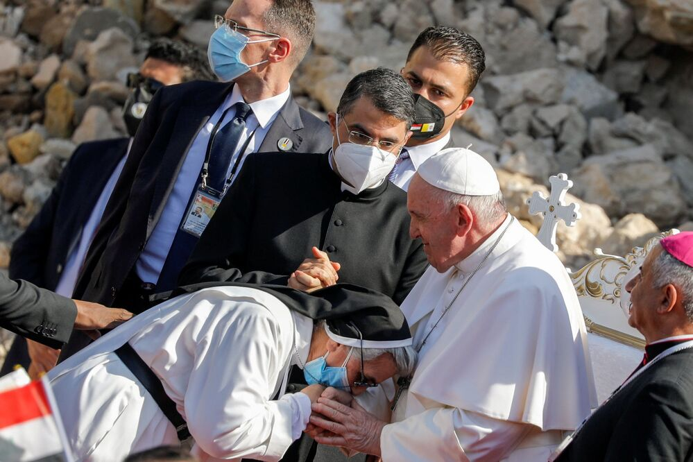 "A nun wearing a protective face mask greets Pope Francis during a prayer for war victims at ""Hosh al-Bieaa"", Church Square, in Mosul's Old City, Iraq, 7 March 2021."
