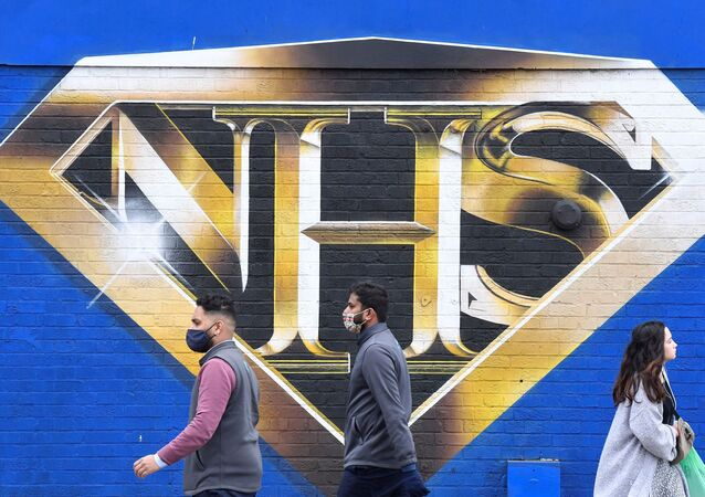 People walk past a mural praising the NHS (National Health Service) amidst the continuation of the coronavirus disease (COVID-19) pandemic, London, Britain, March 5, 2021.