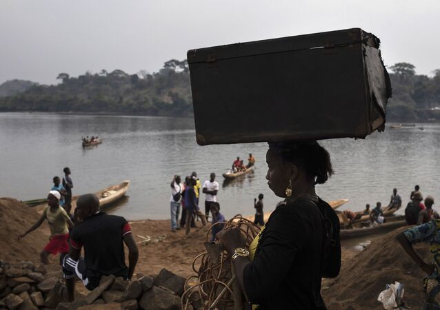 A woman carries her belongings on her head after crossing the Mbomou river back into Bangassou, Central African Republic, from Ndu in the Democratic Republic of the Congo, where she had taken refuge, Sunday Feb. 14, 2021.