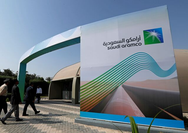 The logo of Aramco is seen as security personnel walk before the start of a press conference by Aramco at the Plaza Conference Center in Dhahran, Saudi Arabia November 3, 2019.