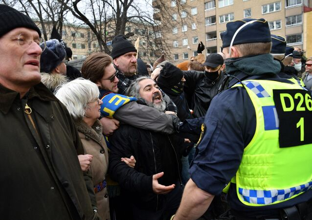 Demonstrators face police as they take part in a protest in Stockholm on March 6, 2021 against the measures taken by the Swedish government to fight the coronavirus (Covid-19) pandemic.