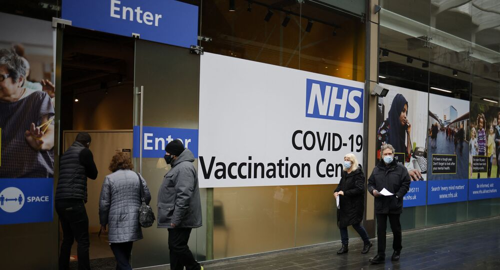 People queue to enter an NHS COVID-19 vaccination centre in Westfield Stratford City shopping centre in east London on February 15, 2021 as Britain's largest ever vaccination programme continues.