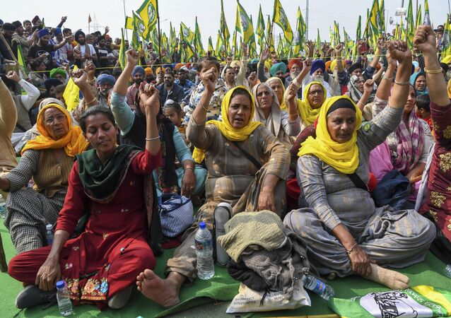 Farmers shout slogans along a blocked highway as they continue their protest against the central government's recent agricultural reforms at Delhi-Uttar Pradesh state border in Ghaziabad on February 2, 2021.