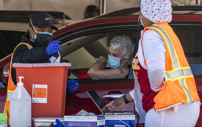 FILE - In this Jan. 26, 2021, file photo, a woman is vaccinated inside her vehicle at a mass COVID-19 vaccination site outside The Forum in Inglewood, Calif. Several states are loosening their coronavirus restrictions on restaurants and other businesses because of improved infection and hospitalization numbers but are moving cautiously, in part because of the more contagious variant taking hold in the U.S.
