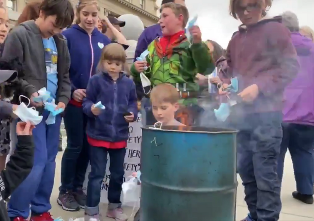 Screenshot capture the weekend demonstration in which parents and guardians encouraged children to remove their masks and throw them into the fire. The demonstration came after state lawmakers passed a measure through the House of Representatives that ban a mask mandate from being implemented in the future.