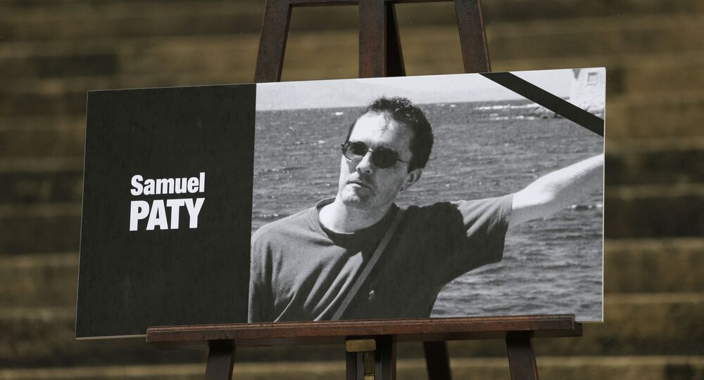 The portrait of slain teacher Samuel Paty with a black ribbon is displayed Tuesday, Oct.20, 2020 on the steps of the National Assembly in Paris.