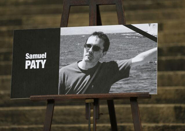 The portrait of slain teacher Samuel Paty is displayed with a black ribbon on the steps of the National Assembly in Paris on  20 October 2020.