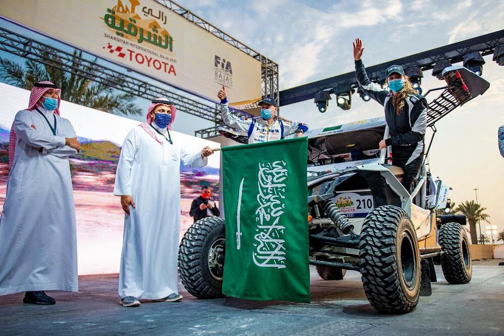 A handout picture provided by Sharqiyah International Baja Toyota on 4 March 2021 shows Saudi driver Dania Akeel, the first-ever Saudi woman to compete in an international rally, waving next to her vehicle in Saudi Arabia.