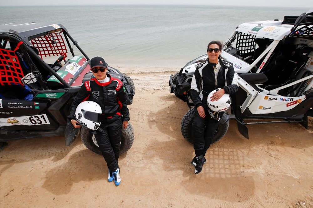 Saudi female rally drivers Mashael Nasser AlObaidan and Dania Akeel pose for a photo next to their buggies during the first stage of the Sharqiyah International Baja Rally, in Dhahran, Saudi Arabia, 5 March 2021.