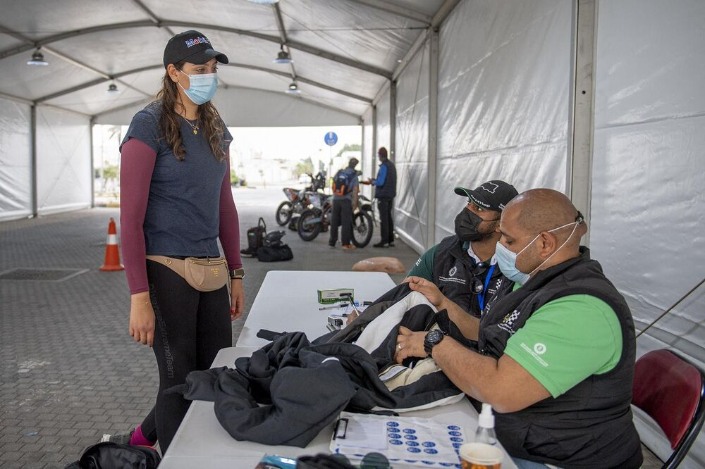A handout picture provided by Sharqiyah International Baja Toyota on 4 March 2021 shows Saudi rider Dania Akeel, the first ever Saudi woman to compete in an international rally, talking to event staff in Saudi Arabia.