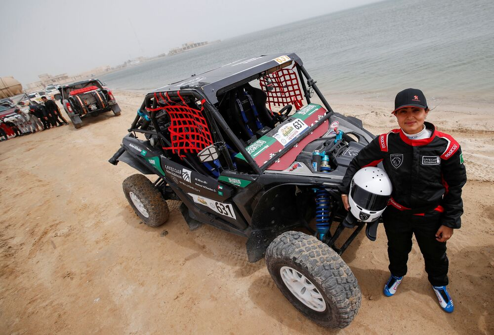 A Saudi female rally driver, Mashael Nasser AlObaidan, poses for a photo next to her T3-Buggy during the first stage of the Sharqiyah International Baja Rally, in Dhahran, Saudi Arabia, 5 March 2021.