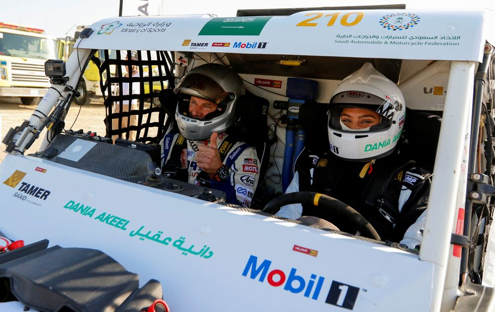 A Saudi female rally driver, Dania Akeel, and her co-driver, Laurent Lichtleuchter, sit in her T1-Buggy during the first stage of the Sharqiyah International Baja Rally, in Dhahran, Saudi Arabia, 4 March 2021.