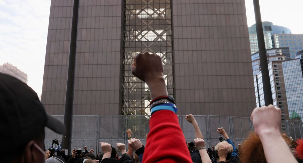 People raise their fists in front of the Hennepin County Courthouse during a rally the day before jury selection is scheduled to begin for the trial of former Minneapolis policeman Derek Chauvin, who is accused of killing George Floyd, in Minneapolis, Minnesota, U.S. March 7, 2021.
