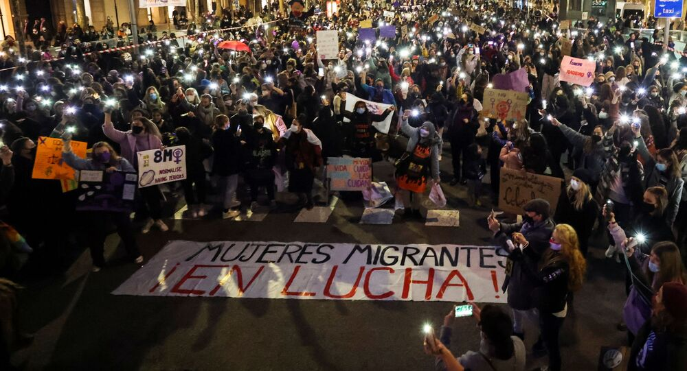 People gather to mark International Women's Day, amid the coronavirus disease (COVID-19) pandemic, in Barcelona, Spain March 8, 2021. The banner reads  Migrant women fighting!