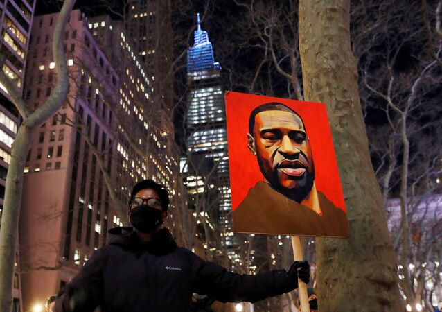 A demonstrator holds up an image of George Floyd during a rally on the first day of the trial of former Minneapolis police officer Derek Chauvin, on murder charges in the death of Floyd, in New York City, New York, U.S., March 8, 2021.