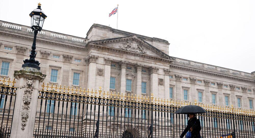 A woman holding an umbrella walks past Buckingham Palace as the snow falls.