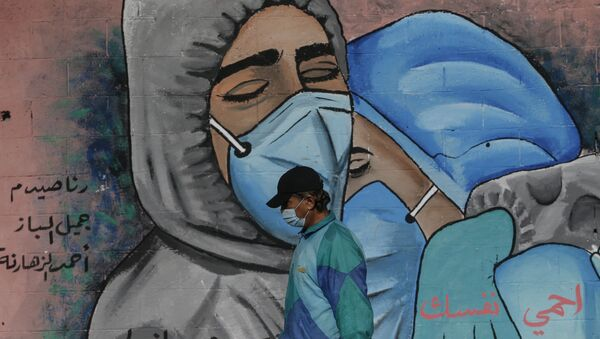 A Palestinian man walks past street art showing doctors mask-clad due to the COVID-19 coronavirus pandemic in the Nusseirat refugee camp in the central Gaza Strip on November 16, 2020.  - Sputnik International