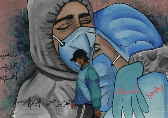 A Palestinian man walks past street art showing doctors mask-clad due to the COVID-19 coronavirus pandemic in the Nusseirat refugee camp in the central Gaza Strip on November 16, 2020.