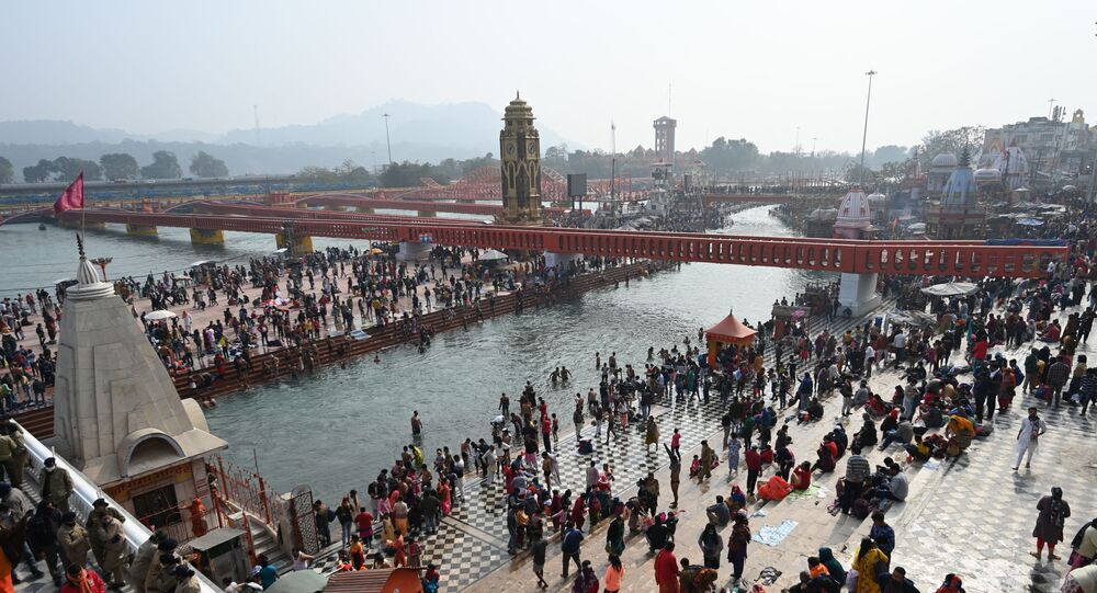 A general view shows Hindu devotees taking a holy dip in the waters of the River Ganges during Makar Sankranti, a day considered to be of great religious significance in the Hindu mythology, on the first day of the religious Kumbh Mela festival in Haridwar on January 14, 2021.