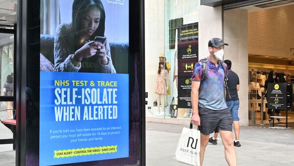 A shopper walks past an advertisment for the UK government's NHS Test and Trace system in Regent Street in London on June 15, 2020 as some non-essential retailers reopen from their coronavirus shutdown - Sputnik International