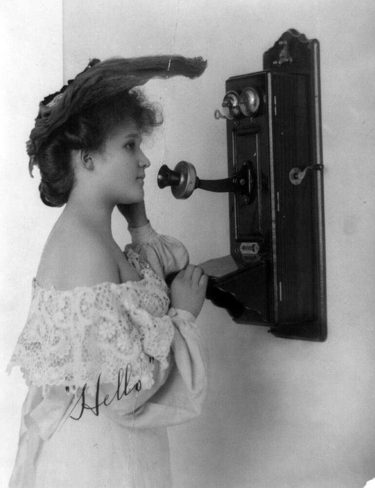 A girl stands in front of an old telephone. The picture dates back to the beginning of the 20th century.