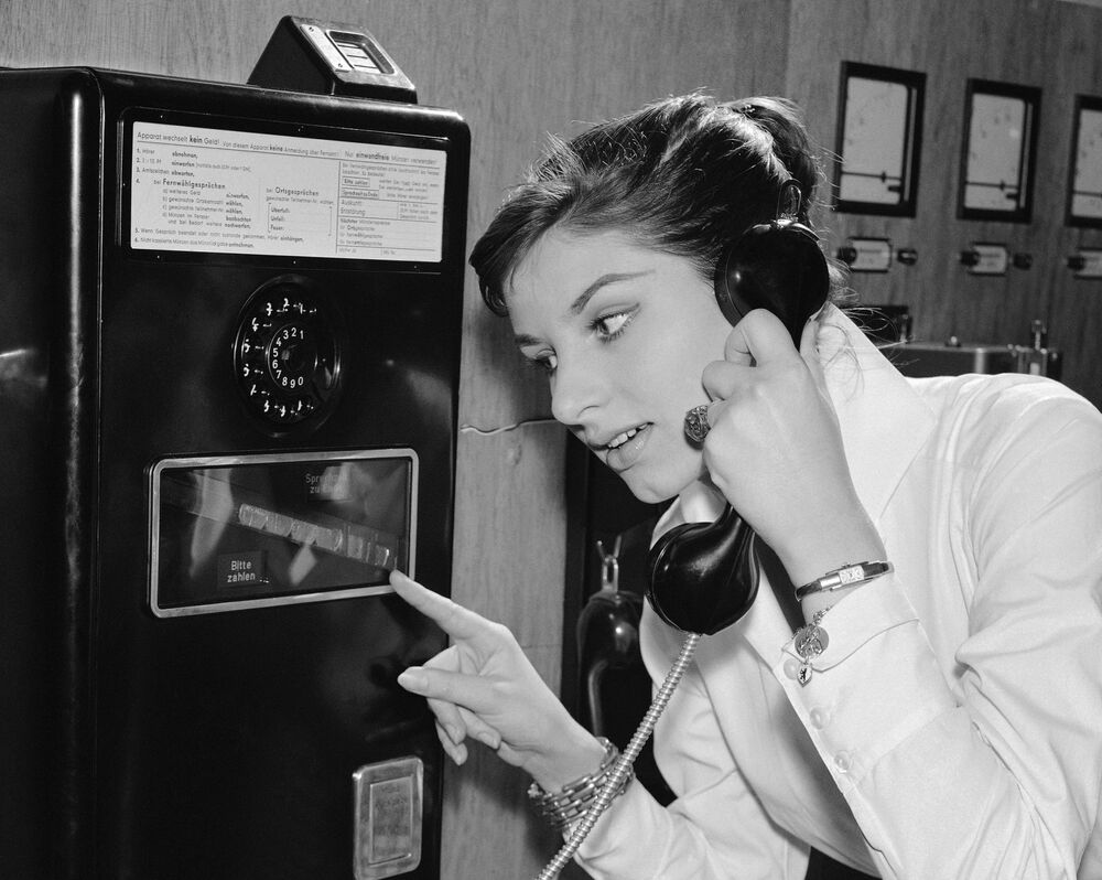 As coins slide down before her eyes, a German woman uses a new long distance dial telephone for public booths, 17 July 1957.