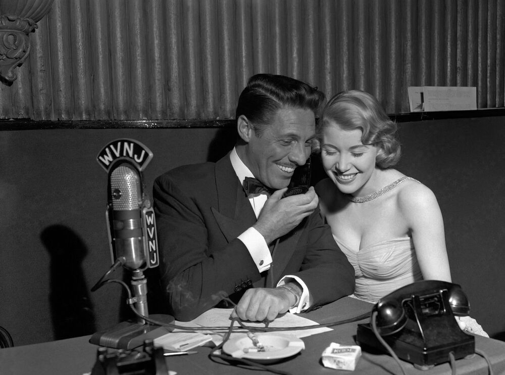 French singer Jean Sablon (L) talks over the telephone with listeners during disc jockette Vy Prosser's (R) radio broadcast in New York on 16 March 1949. Sablon  the same day opened a limited engagement at the New York nightclub Versailles.