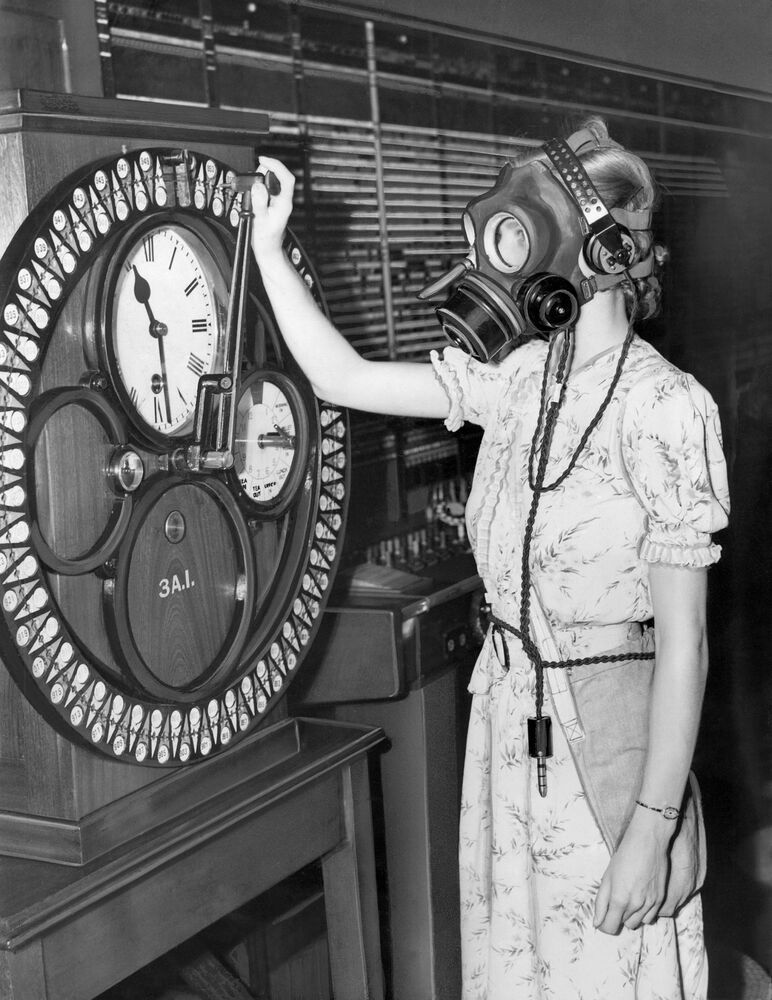 A London telephone operator demonstrates a special gas mask, equipped with built-in microphone and earpieces so that she can continue working even in the event of an air or gas raid. Here she punches a time clock. The demonstration took place at the Faraday Building trunk exchange, London, on 3 August 1938.