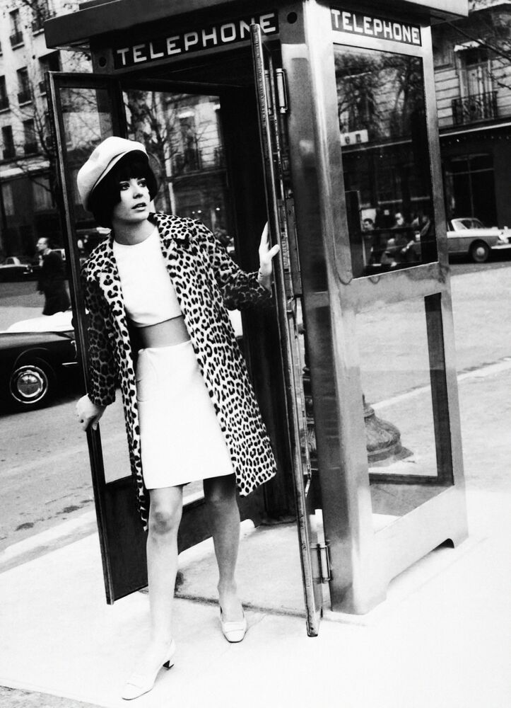 A model wearing a two-piece Carven suit poses in a telephone booth on the Champs-Elysees in Paris on 17 February 1969.