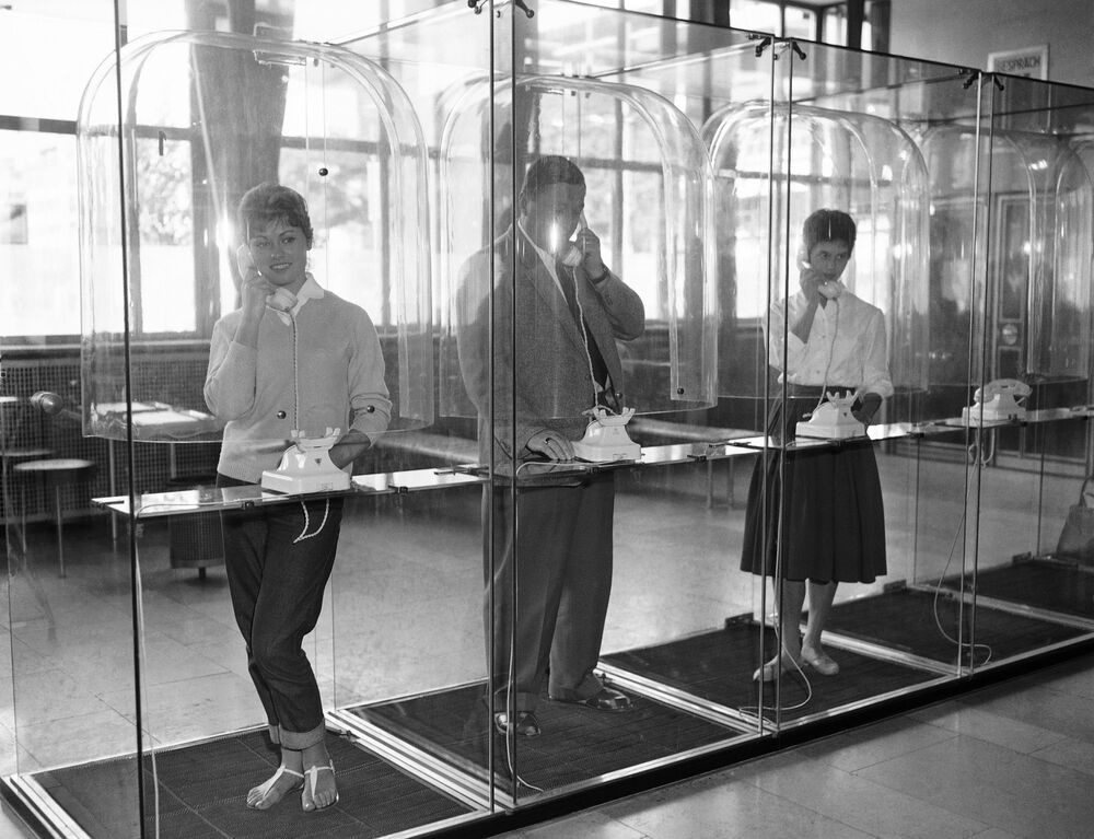 Three people make telephone calls from transparent phone booths in a post office in Mannheim, West Germany, 8 October 1959.  It was hoped the booth would make callers more aware of other people waiting and thus shorten their calls.