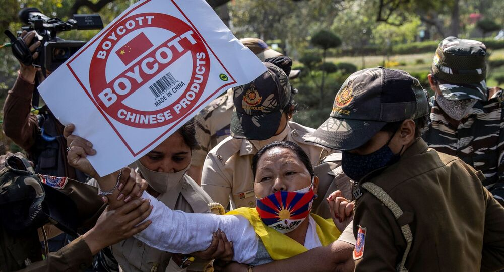 A Tibetan holds a placard as she is detained by police officers during a protest held to mark the 62nd anniversary of the Tibetan uprising against Chinese rule, outside the Chinese Embassy in New Delhi, India March 10, 2021