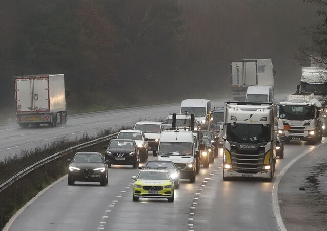 Traffic including freight lorries drive under police escort to manage the traffic on the M20 motorway which leads to the Port of Dover at Mersham in Kent, south east England on December 21, 2020, as a string of countries banned travel including accompanied freight arriving from the UK, due to the rapid spread of a more-infectious new coronavirus strain. - Britain's critical south coast port at Dover said on Sunday it was closing to all accompanied freight and passengers due to the French border restrictions until further notice.