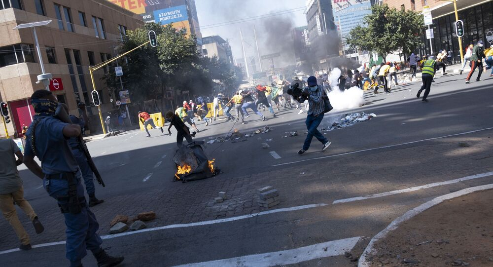 South African Police Service (SAPS) officers use teargas to disperse students during a protest in Braamfontein, Johannesburg, on March 10, 2021. - A man was shot dead on March 10, 2021 after police moved to disperse students protesting over the financial exclusion, the state broadcaster reported, as a funding crisis sweeps over universities