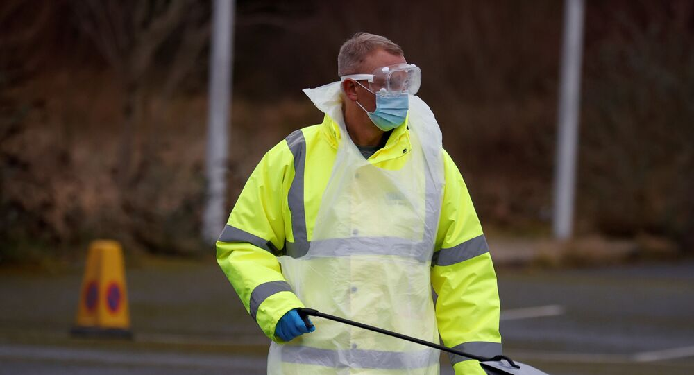 A member of NHS Test and Trace staff carries a testing kit as they arrive at a mobile testing centre amid the outbreak of the coronavirus disease (COVID-19) in Southport, Britain, February 3, 2021.