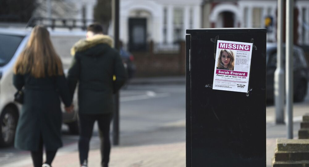 A couple walk past a poster in south London appealing for help in finding missing Sarah Everard