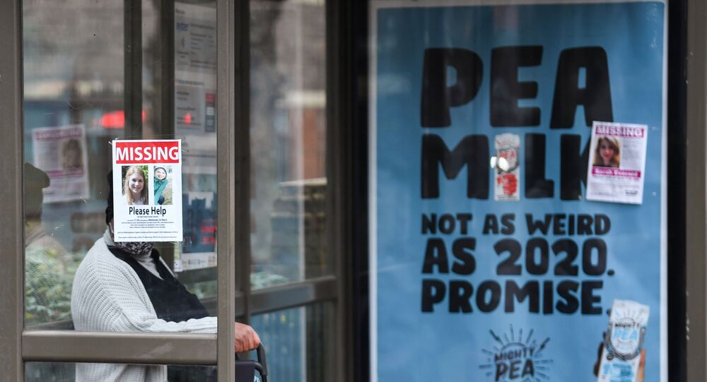 A person sits at a bus stop next to signs that show pictures of Sarah Everard, who disappeared last week, as police continue to search parts of Clapham, in London, Britain, March 10, 2021