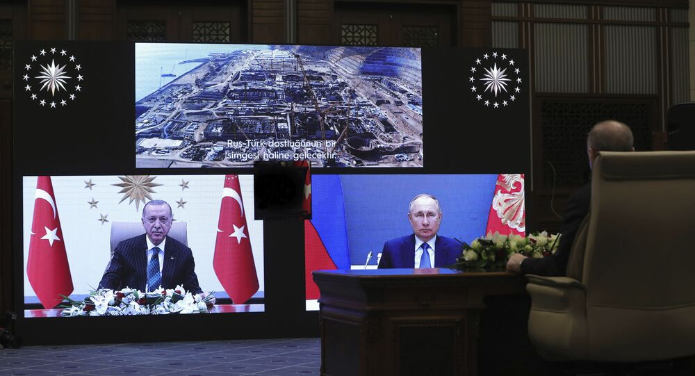 Turkey's Recep Tayyip Erdogan sitting extreme right, and on screen bottom left, with Russia's President Vladimir Putin, bottom right, speak during a ceremony as they have remotely inaugurated the construction of a third nuclear reactor of Akkuyu power plant in Mersin province on the Mediterranean coast, in Ankara, Turkey, Wednesday, March 10, 2021. Erdogan called the plant a symbol of Turkish-Russian cooperation.