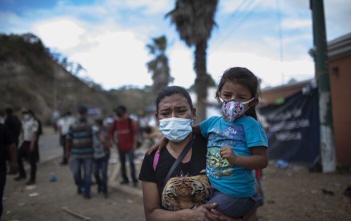 A woman and a girl walk away as Honduran migrants confront Guatemalan soldiers and police blocking them from advancing toward the US, on the highway in Vado Hondo, Guatemala, Monday, Jan. 18, 2021. The roadblock was strategically placed at a chokepoint on the two-lane highway flanked by a tall mountainside and a wall leaving the migrants with few options.