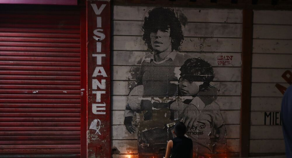 A boy kneels in front of a mural of Diego Maradona decorated with canddles outside the stadium of Argentinos Juniors soccer club, where he started as a professional footballer, in Buenos Aires, Argentina, Wednesday, Nov. 25, 2020. The Argentine soccer great who was among the best players ever and who led his country to the 1986 World Cup title died from a heart attack on Wednesday at his home in Buenos Aires. He was 60.
