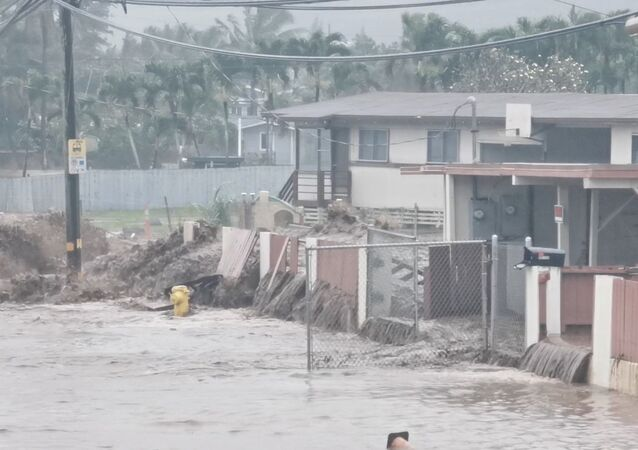 Social media video grab shows floodwaters streaming down a street in Hauula, Hawaii