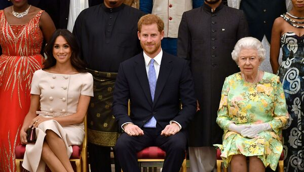 Britain's Queen Elizabeth, Prince Harry and Meghan, the Duchess of Sussex pose for a picture with some of Queen's Young Leaders at a Buckingham Palace reception following the final Queen's Young Leaders Awards Ceremony, in London, Britain June 26, 2018 - Sputnik International