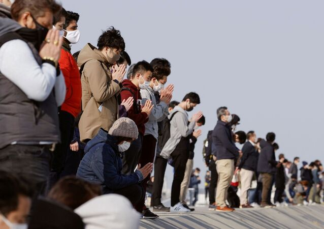 Participants pray and observe a moment of silence towards the sea at 2:46 p.m. (05:46 GMT), the time when the 9.0-magnitude earthquake struck off Japan's coast in 2011, at Arahama district in Sendai, northeastern Japan, March 11, 2021, to mark the 10-year anniversary of the 2011 earthquake and tsunami that killed thousands and set off a nuclear crisis