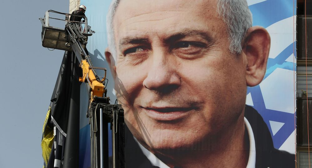 A labourer hangs a Likud party election campaign banner depicting party leader Israeli Prime Minister Benjamin Netanyahu, ahead of a March 23 ballot, in Jerusalem March 10, 2021